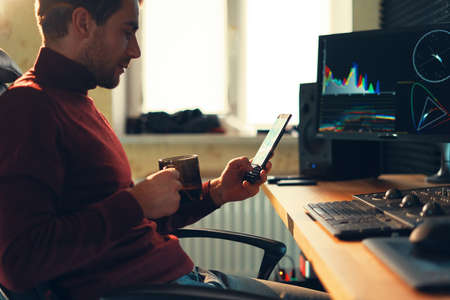 Young man working in the studio using a smartphone and computer. Caucasian freelancer holding mobile phone working on footage, video, design.