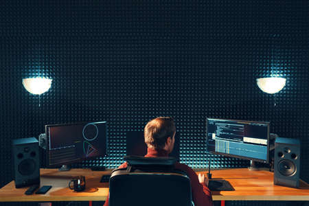 Video editing. Professional editor adding special sound effects. Back view of young man watching graphs on monitors. Copy space on gray wall Stockfoto
