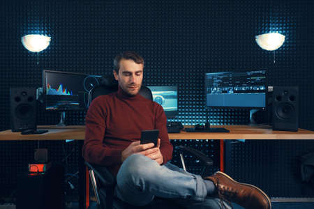 Young man working in the studio using a smartphone and computers. Caucasian freelancer holding mobile phone sitting leg over leg.