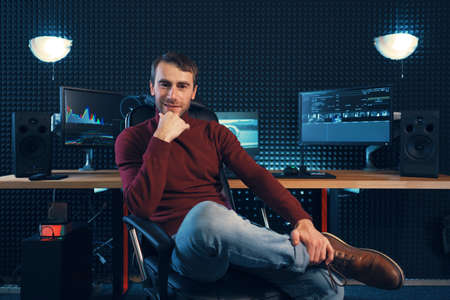 Successful designer or editor sitting leg over leg in a leather armchair looking to camera, with monitors and soundproofing wall in background with copy space