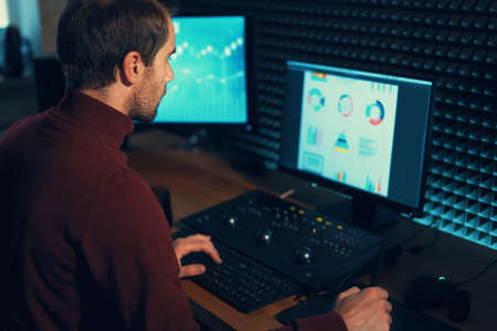 Zelfverzekerde Man Video Editor werkt met beelden in Creative Office Studio. Stockfoto