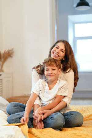 Mom and son smiling, hugging, having fun, spend time together in a relaxing atmosphere at home while sitting