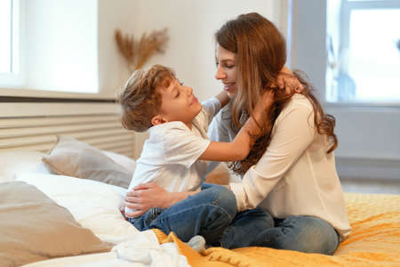 Mom and son smiling, hugging, looking at each other, having fun in a relaxing atmosphere at home while sitting Stock Photo