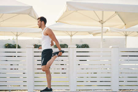 Young smiling fitness runner stretching legs before run. Athletic male getting ready for jogging outdoors. Copy space on left.m Archivio Fotografico