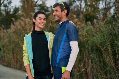 Happy sporty couple portrait. Man and woman smiling at each other while hugging. Runners outside resting after running. Stock Photo