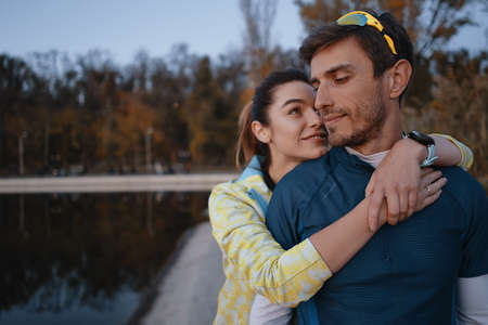 Happy sporty couple portrait. Man and woman smiling while hugging. Runners outside resting after running.
