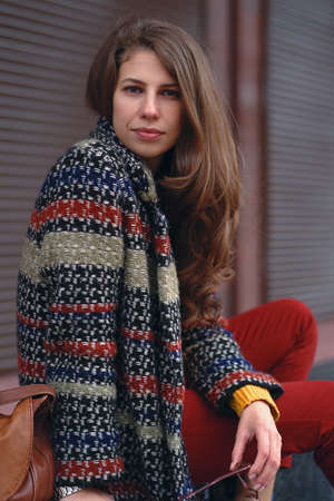 Portrait of young, beautiful woman wearing a stylish coat, red pants, orange sweater,  with a brown leather bag, posing in street of a European city.