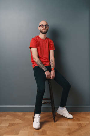 Confident stylish young bearded man wearing glasses with black frame, posing in studio o gray background while sitting on a tall chair.