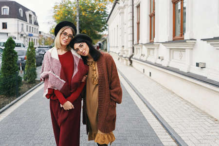 Carefree fashionable women models in elegant autumn clothes and glasses. Young fashion girls in stylish woven wool clothes and hats over urban city background, autumn portrait.