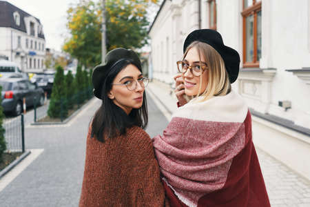 Happy moments with two stylish girls, looking over shoulder, smiling, walking on a street in the city. Closeup portrait, funny, joyful attractive young women having fun, best friends, sisters.