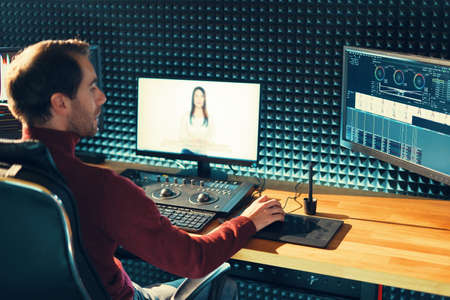 Confident Man editing video in his Studio. Banco de Imagens