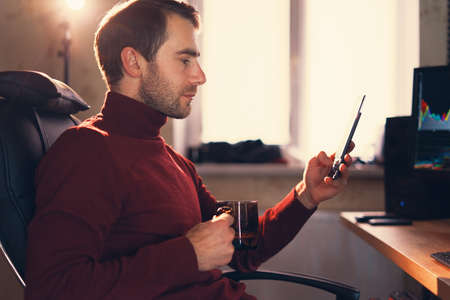 Young man working in the studio using a smartphone.