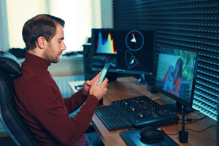 Young man working in the studio using a smartphone in front of the computer