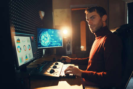 Confident Man Video Editor Works with Footage in Creative Office Studio. Stock Photo