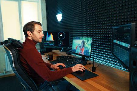 Confiant Man Video Editor fonctionne avec des images dans Creative Office Studio.