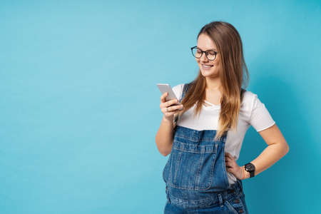 Maternity concept. Smiling pregnant woman, with glasses, holding a mobile phone in one hand. Portrait of the future mom using technology with copy space for writing over blue background