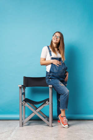 Pregnant woman caressing her belly while sitting on a tall chair in studio over blue background. A cute young woman wearing glasses, and denim romper touching tummy communicating with unborn child. Stok Fotoğraf