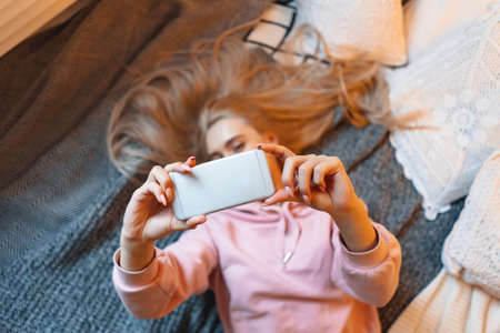 Pretty young girl having fun, making selfie while lying on the bed at home. Top angle view. Charming Caucasian woman taking picture of herself, for her friends and fans, for social media.