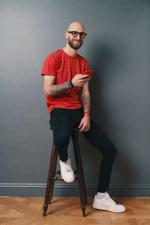 Handsome hairless Caucasian man with beard, glasses, red T-shirt texting while holding smartphone in his tattooed arms, smiling, he is posing while sitting on a tall chair