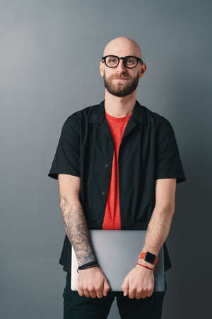 A responsible young bearded man with glasses holding laptop under his arms in the studio on gray background. Stylish designer, offer a better design experience to his clients.
