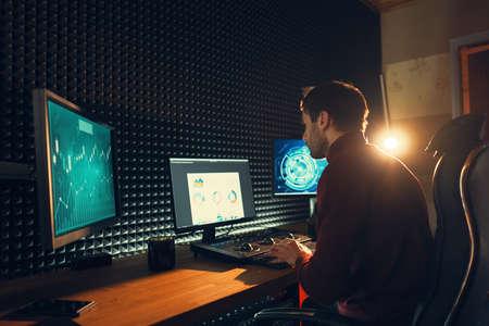 Confident Man Video Editor współpracuje z materiałem filmowym w Creative Office Studio ze światłem w tle.