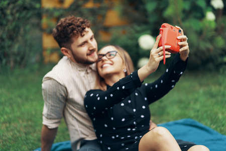 Young couple in love taking a selfie with an instant camera. Lying on the grass in the yard of his house Foto de archivo - 130818201