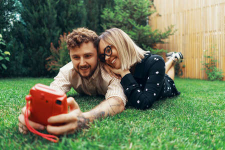 Young couple in love taking a selfie with an instant camera. Lying on the grass in the yard of his house
