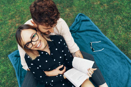 Couple in love lying on the grass in the yard of his house. Girl reading a book 스톡 콘텐츠