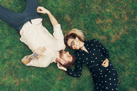 Couple in love lying on the grass in the backyard of their own home. View from the top Foto de archivo - 130818217