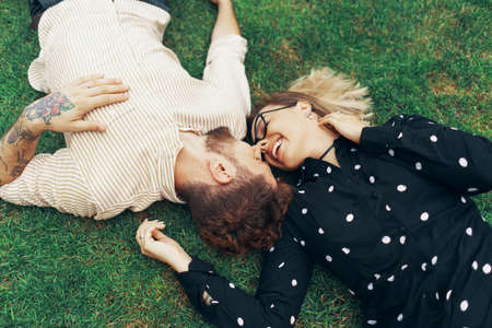 Couple in love lying on the grass in the backyard of their own home. View from the top Reklamní fotografie
