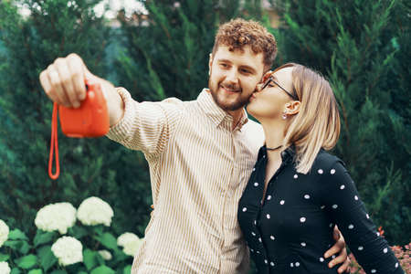 Young couple in love taking a selfie with an instant camera, in the yard of his house Foto de archivo - 130818243