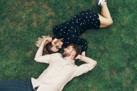 Couple in love lying on the grass in the backyard of their own home. View from the top Foto de archivo - 130818245