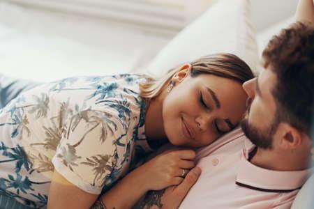 Pareja de enamorados abrazándose en la cama. Hombre abrazando y besando a su novia Foto de archivo