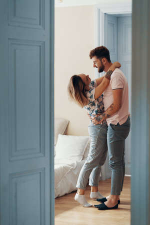 Profile view of loving young couple hugging while standing in their bedroom. View from another room through the doorway Reklamní fotografie - 130818251
