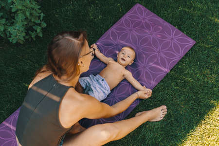 Mother doing baby yoga for her son on a mat in the backyard