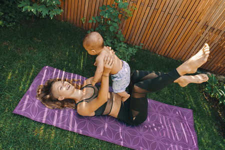 Mother doing baby yoga for her son on a mat in the backyard 스톡 콘텐츠 - 130818287