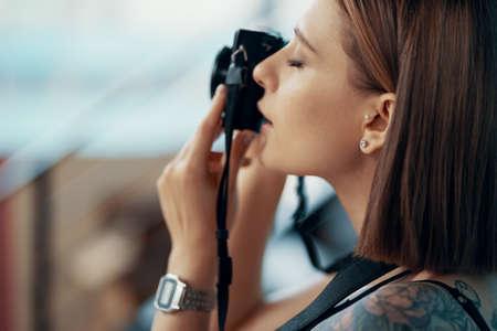 Stylish young girl photographer taking photos on blue background