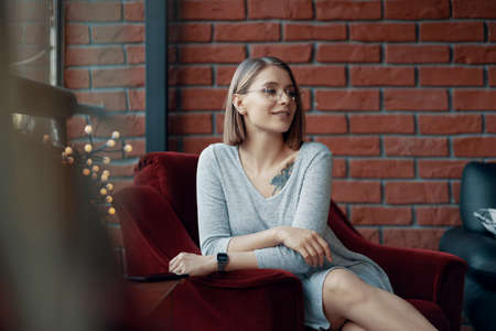 Portrait of an attractive girl sitting in a red cozy chair opposite a large window. Loft Interior