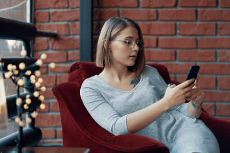 Attractive girl sits in a red cozy chair with a mobile phone in his hand