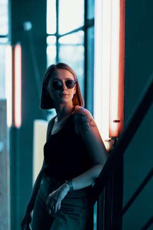 Fashion portrait of young attractive girl in sunglasses. Neon light