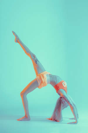 Athletic young woman doing yoga exercise. Dressed in retro sportswear. Neon lights. Specific studio light