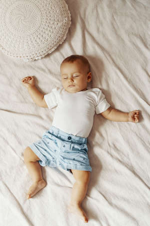 Adorable baby sleeping on white bed with copy space Foto de archivo