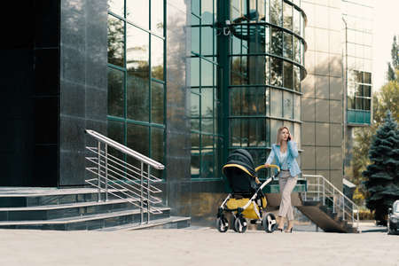 Portrait of a successful business woman in blue suit with baby. Business woman talking on the phone and pushing baby stroller