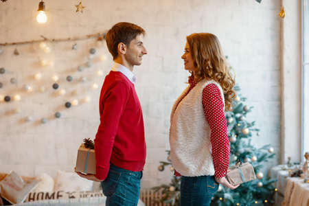 Man and woman hiding Christmas present boxes behind back looking to each other with Christmas decorations in background