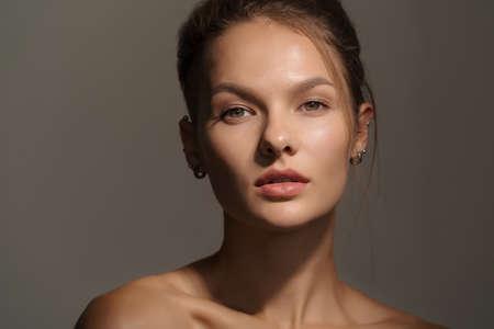 Retrato de una chica joven impresionante con la piel limpia sobre fondo oscuro. Tiro del estudio de la señorita. Retrato de primer plano de una mujer de aspecto serio Foto de archivo
