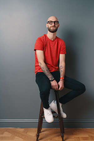 Smiling bearded young man on gray background. Stylish man wearing glasses, looking at camera and laughing while sitting on a tall chair. Foto de archivo