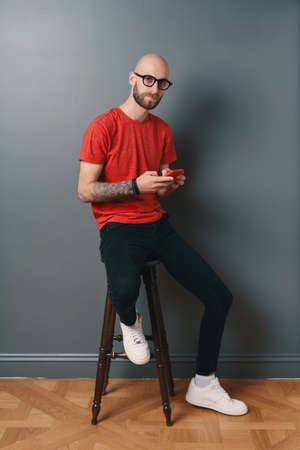 Handsome hairless Caucasian man with beard, glasses, red T-shirt, texting while holding smartphone in his tattooed arms while looking at the camera, over gray studio background.
