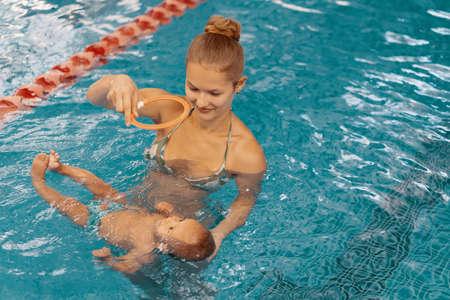Giovane madre e il suo bambino che si godono una lezione di nuoto per bambini in piscina. Bambino che si diverte in acqua con la mamma Archivio Fotografico