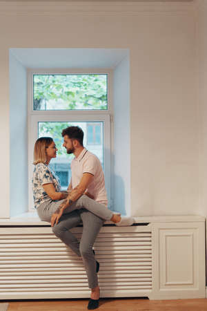 Couple in love sitting on the windowsill