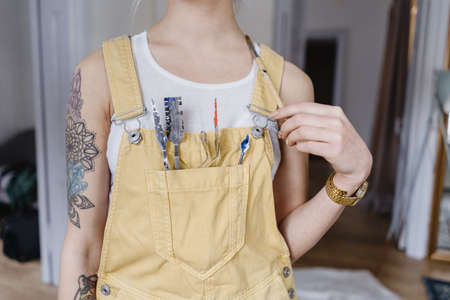 Closeup young female artist holding painting instruments in a pocket on the bust indoors. Tattoos on hands.